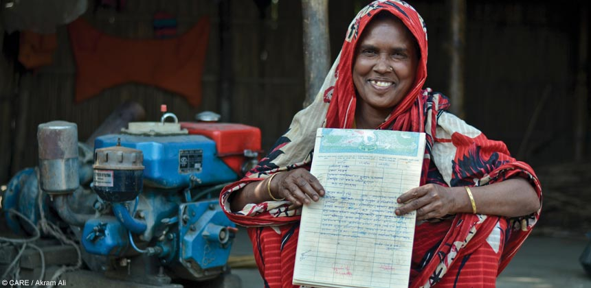 A woman in Bangladesh shows off a land title