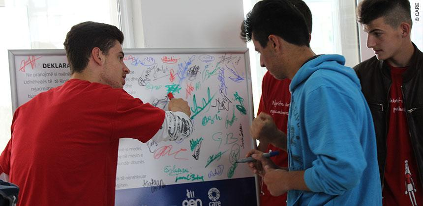 Youths in the Be A Man session signing a declaration 'to always take a stand against violence and harassment' © CARE